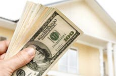 Close up of a hand holding cash in front of a house © Kuzma/Shutterstock.com