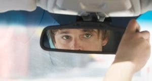 Man looking into rear-view mirror | Jamie Grill/Getty Images