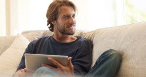 Man relaxing with a tablet on the couch | CaiaImage/Getty Images