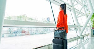 Woman looking out of airport window © iStock
