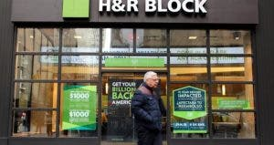 Man walking past storefront of H&R Block | Northfoto/Shutterstock.com