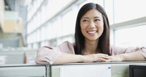 Smiling young woman in work office | Hero Images/Getty Images