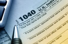 Tax form 1040 in blue and yellow lighting © Robyn Mackenzie/Shutterstock.com