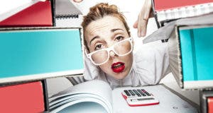 Secretary or accountant stressed at paperwork © ndphoto/Shutterstock.com