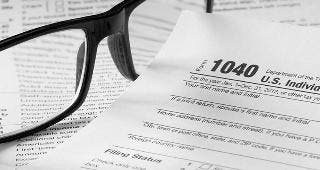Form 1040 with glasses and pen © topseller/Shutterstock.com