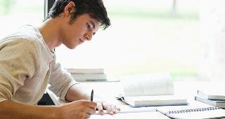 Young man writing at desk © wavebreakmedia/Shutterstock.com