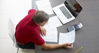 Man doing paperwork © Diego Cervo/Shutterstock.com