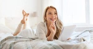 Woman writing notes on bed | Syda Productions/Shutterstock.com