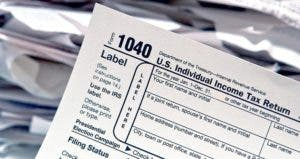 1040 tax forms with stacks of papers on background © Olivier Le Queinec/Shutterstock.com