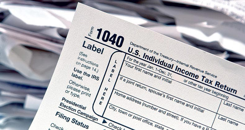 1040 tax form with stacks of papers on background mst