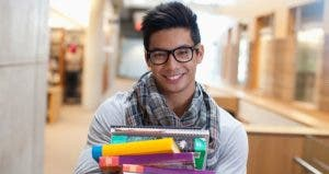 Male student holding textbooks | Sam Edwards/Getty Images