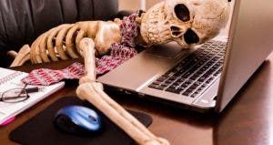 Skeleton slumped on notebook computer in office © iStock