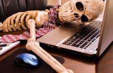 Skeleton slumped on notebook computer in office © iStock