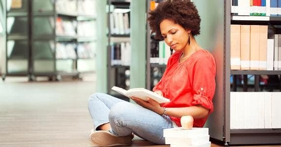 Female college student reading in library