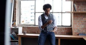 Man leaning against desk, looking at phone   Lilly Roadstones/Getty Images