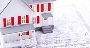 Toy house on top of 'Sign here' section of tax form © iStock