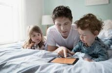 Dad and kids browsing tablet computer | Hero Images/Getty Images