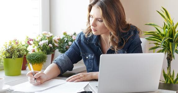 Woman wearing denim jacket filling up paperwork