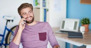 Young man in purple shirt on a phone call | gpointstudio/Getty Images