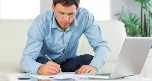 Man doing paperwork in living room © wavebreakmedia/Shutterstock.com