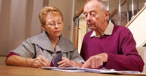 Two seniors looking at their checkbook © iStock
