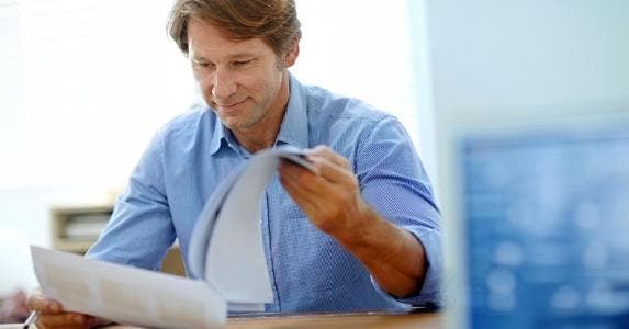 Smiling middle aged man reading paperwork © iStock