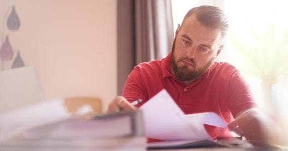 Man in red shirt reading letter | Martin Prescott/Getty Images