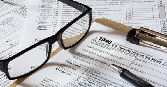 Tax forms on clipboard with glasses and pen © topseller/Shutterstock.com