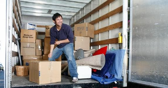 Man happily unloading boxes from boxtruck | John Eder/Getty Images