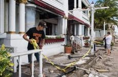 Man removing yellow caution tape from damaged home | The Washington Post/Getty Images