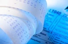 Tax form 1040 and receipt | iStock/Enrico Fianchini
