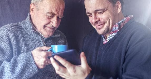 Father and son looking at smartphone display © iStock