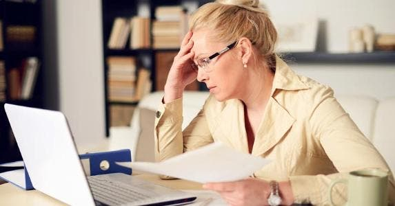 Woman slumping over her home office desk © iStock