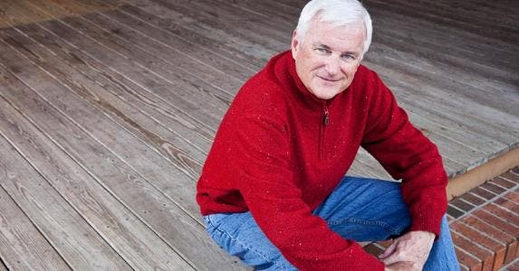Senior man sitting on front porch steps © iStock