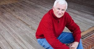 Senior man sitting on front porch steps © iStock