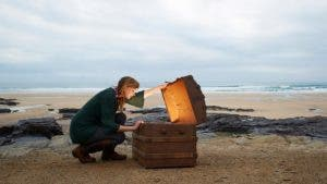 Woman cracking open a chest on the beach | Dougal Waters/Getty Images