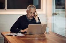 Mature man in dining room reading laptop | iStock.com/PeopleImages