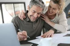 Couple signing paperwork at home | goodluz/Shutterstock.com