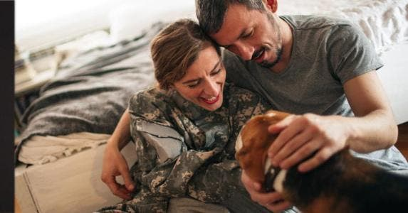 A couple petting their dog   AleksandarNakic/E+/Getty Images