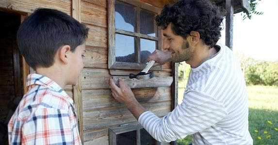 Father hammering wood onto cabin with son | Maria Teijeiro/Getty Images