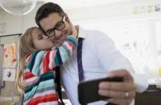Father taking a selfie with his daughter | Hero Images/Getty Images