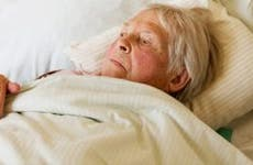 Elderly woman laying on bed | SilviaJansen/E+/Getty Images