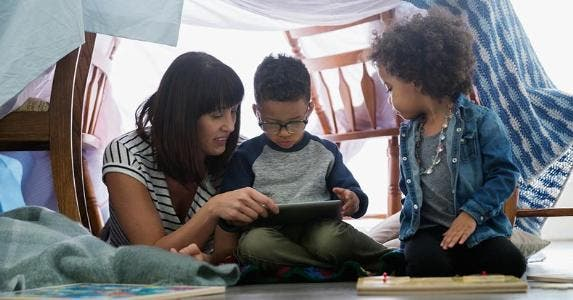 Mother reading to her sons, under a blanket fort | Hero Images/Getty Images