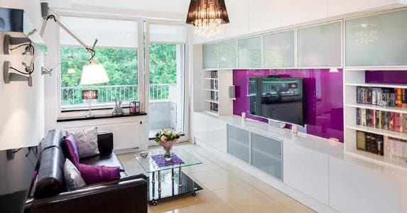 Modern apartment living room with purple TV wall | Jacek Kadaj/Getty Images