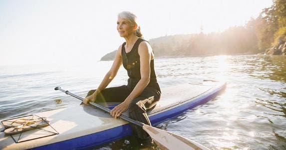 Senior woman sitting on kayak | Hero Images/Getty Images