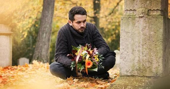 Man mourning loved one at graveyard | ajkkafe/Getty Images