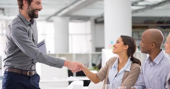 Employees shaking hands | PeopleImages.com/Getty Images