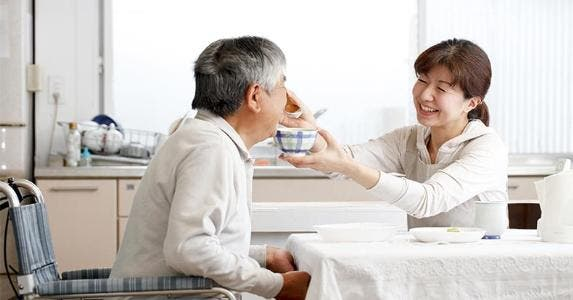 Daughter feeding her father a bowl of soup © kazoka/Shutterstock.com