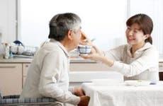 Daughter feeding her father a bowl of soup © kazoka/Shutterstock.com