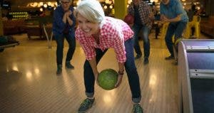 Mature woman and friends bowling | Hero Images/Getty Images